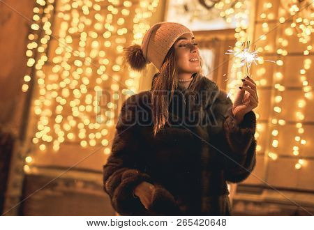 Beautiful young woman in fur coat holding a sparkler enjoys winter Christmas mood in old snowy European city on festive yellow lights bokeh background stock photo