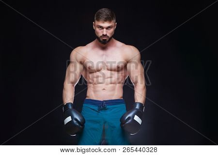 Strong muscular boxer in black boxing gloves. Isolated on black background. stock photo