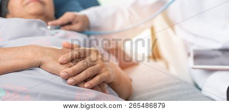 Hospitalized Elderly Patient, Senior Old Aging Woman Laying On Bed With Cardiologist Doctor Or Physi