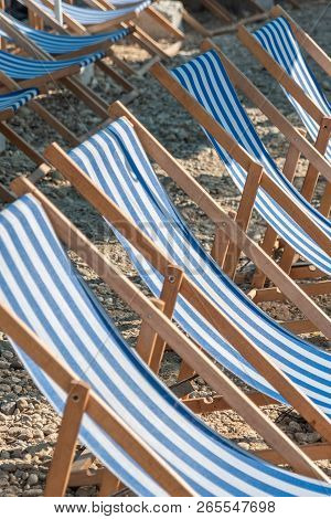 Blue and white wooden Deckchairs on a sandy beach opened. ready for sunbathing. stock photo