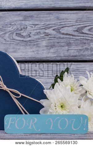 Romantic composition on wooden background. Close up heart-shaped gift boxes, flowers and paper card on rustic wood. Happy Valentines Day. stock photo