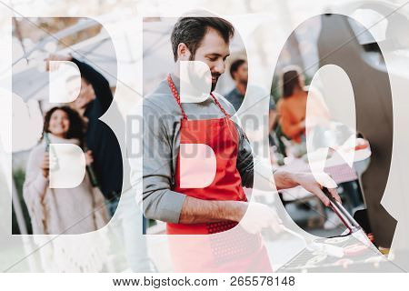Beautiful Caucasian Man Is Grilling Barbecue. Smoked Food. Nature Activity. Outside Relaxing Concept. Smiling Friends Are Making A Selfie. Resting Together. Drinking Beer Couple Backstage. stock photo