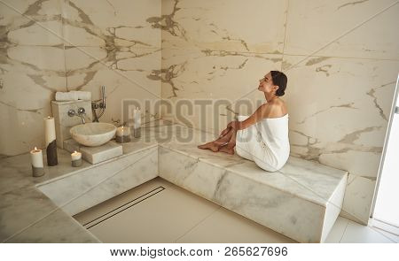 Happy lady putting her head up and smiling cheerfully in hammam stock photo