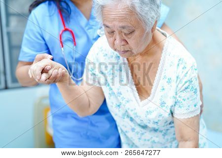 Asian nurse physiotherapist doctor care, help and support senior or elderly old lady woman patient get up from bed at hospital ward : healthy strong medical concept. stock photo