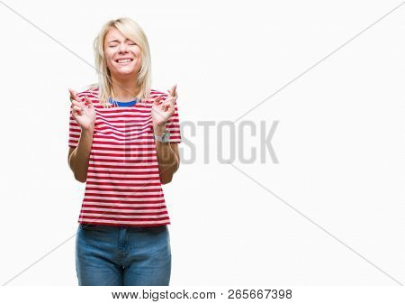Young beautiful blonde woman over isolated background smiling crossing fingers with hope and eyes closed. Luck and superstitious concept. stock photo