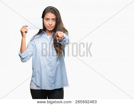 Young arab woman holding blank card over isolated background pointing with finger to the camera and to you, hand sign, positive and confident gesture from the front stock photo