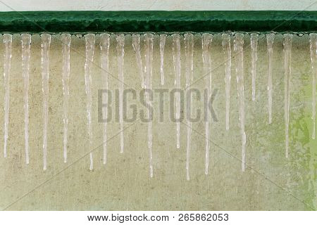 Icing of outdoor steel piping at winter season. Icy icicles gutter after thaw. stock photo