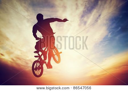 Man jumping on bmx bike performing a trick against sunset sky. Extreme sport stock photo
