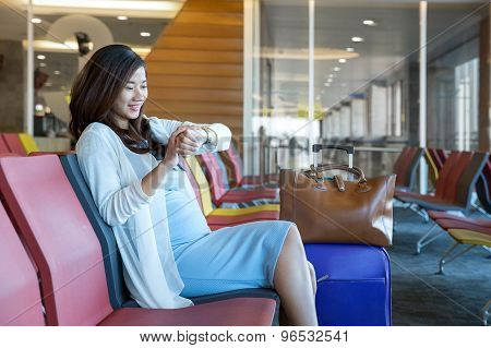 Woman in the aiport lounge sitting in chair by the window looking at her watch waiting for her schedule to fly stock photo