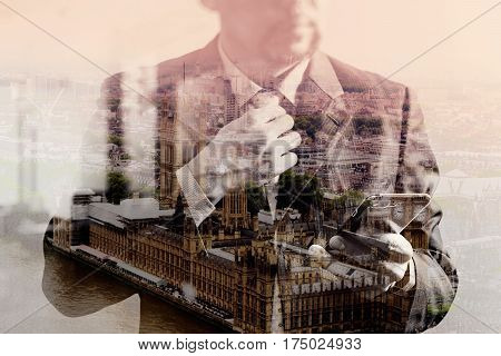 double exposure of success businessman holding tie and using smart phonethinkingfront viewfilter effectLondon buildings city stock photo