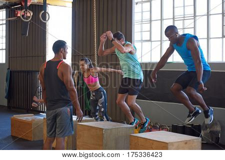 Crossfit class jumping on wooden boxes guided by trainer, strength training fitness workout in gym
