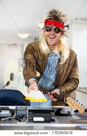 Rockstar with a guitar holding out tickets for his gig in his outstreched arm behind the counter of a ticket booth stock photo