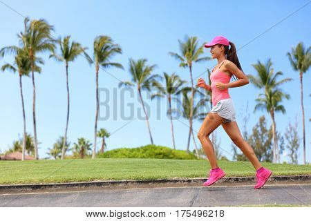 Healthy woman runner jogging on city sidewalk. Happy Fitness girl athlete working out living an active lifestyle training cardio in the morning running in pink sportswear, cap and shoes. Full body. stock photo