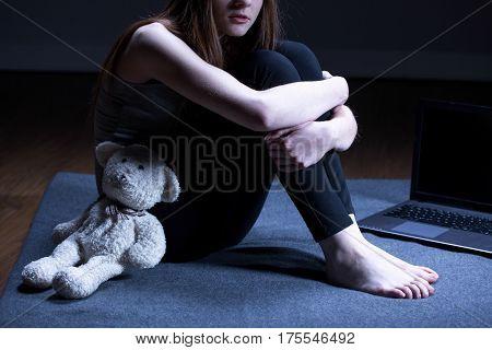 Molested girl with teddy bear sitting on floor stock photo