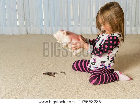 Young girl on floor of home trying to get money to pay off debt  out of a piggy bank for expenses in the future stock photo