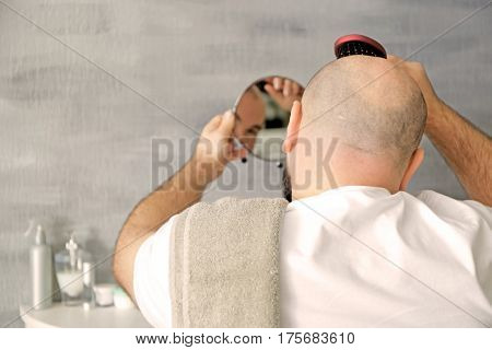 Bald adult man with hair brush looking in mirror at home stock photo