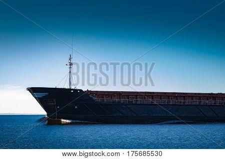 Black cargo ship's bow. Bulk carrier sailing in still Baltic sea stock photo
