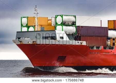 Red cargo container ship's bow in cloudy day stock photo