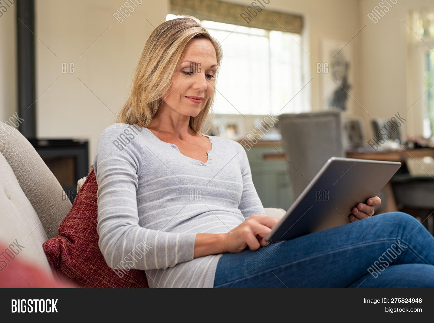 40s,beautiful,blonde hair,browsing,casual,caucasian,checking account,checking email,cheerful,communication,computer,connection,connectivity,digital,digital tablet,ebook,entertainment,happy,holding,holding ipad,home,indoors,internet,laptop,leisure,looking,mature,media,mid,mid adult woman,middle aged woman,people,pretty,read,relax,relaxing at home,sitting,sitting on couch,smiling,social,sofa,tablet,technology,using,using laptop,using tablet,watching,wifi,wireless,woman