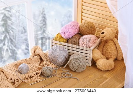 Woolen yarn and fabric on the window sill. Beautiful view outside the window - winter scenery and snow. stock photo