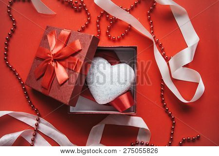 Red box and heart inside on red background. Concept for Valentines Day or Womens Day. stock photo