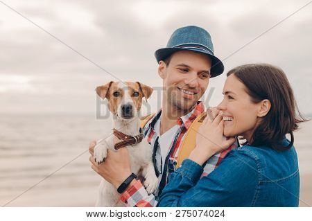 People, vacation concept. Horizontal shot of pleased young woman and man dressed in hat and shirt, carry pedigree dog, have fun together, pose against clear sky near sea, have positive expressions stock photo