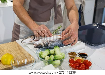 Chief putting thyme in raw fish before cooking in light kitchen. Preparing trout for baking in roasting tray. Family dinner on holidays. Cooking in cozy cuisine at home stock photo