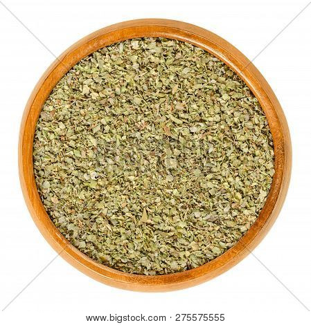 Dried marjoram in wooden bowl. Origanum majorana, also sweet, knotted or pot marjoram. Green herb and spice with sweet pine and citrus flavors. Macro food photo closeup from above on white background. stock photo