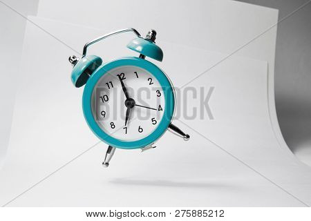 The blue alarm clock bounces against the background of business papers. stock photo