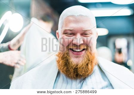 A red bearded man is very happy to have shaved of his head in barbershop. stock photo