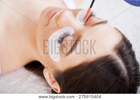 Eyelashes extensions. Fake Eyelashes. Eyelash Extension Procedure. Professional stylist lengthening female lashes. Master and a client in a beauty salon stock photo