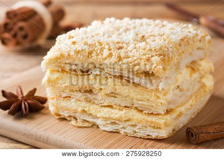 Layered cake with cream Napoleon millefeuille vanilla slice with cinnamon and anise on wooden background. stock photo