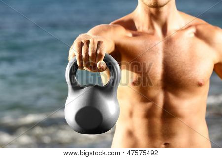 fitness man training with kettlebells outtside. Kettlebell closeup of fit male sport athlete strength training shoulder and arms outdoors on beach. stock photo