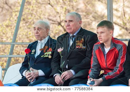 Senior veterans of World War II and boy on tribune