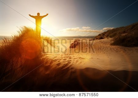 Silhouette of a man with hands raised in the sunset on a beach concept for religion, worship, prayer