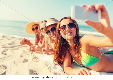 summer vacation, travel, technology and people concept - group of smiling women in sunglasses and ha