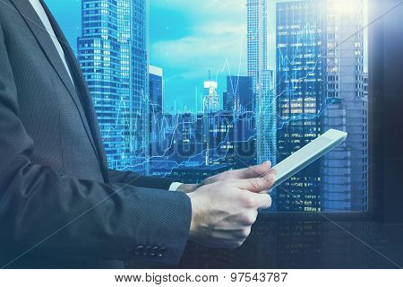 Close-up of side view of a businessman who is browsing on his tablet. Panoramic Manhattan evening view New York. Forex chart is over the cityscape. Toning filter. stock photo