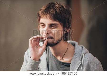 Closeup of young man smoke marihuana grass or hashish joint cigarette in abandoned ghetto part of the city stock photo