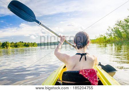 View on girl riding kayak on Amazon river by Leticia in Colombia stock photo
