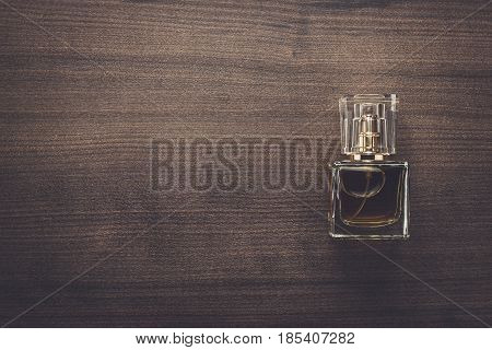Perfume bottle over wooden background. Perfume bottle on the table. Men\'s perfume bottle with copy space. Square shaped perfume bottle