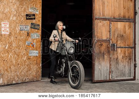 woman pulls her bike. Motorcycle in the garage. A woman in a leather jacket. stock photo