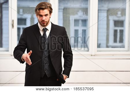 man offer cooperation or businessman with beard on serious face in black jacket tie on window background business concept stock photo