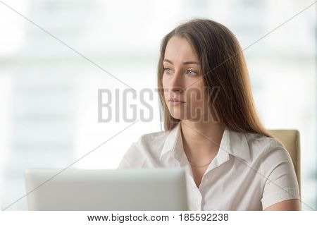 Lost in thoughts businesswoman thinking of solution. Worried female sitting alone in office looking away. Female entrepreneur ponders decision at workplace. Absent minded young woman tired, distracted stock photo