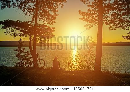Summer evening near the lake. Summer silhouette landscape - unidentified tourist girl with bicycle near the Irtyash Lake in Southern Urals.Summer landscape. Concept of summer activities. Sunny summer background. Sunset summer nature