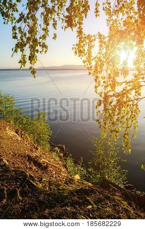 Summer sunset water landscape of Irtyash Lake in Southern Urals Russia.Summer lake in sunny evening. Sunny summer landscape of summer lake waters framed by summer trees. Sunny summer water landscape nature stock photo