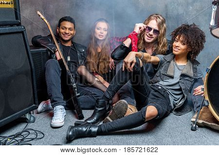 Rock Band Sitting On Floor While Resting After Rehearse In Studio, Rock And Roll Band Concept