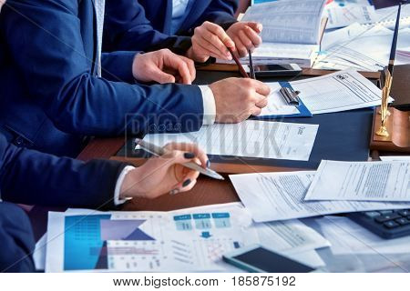 Business people office life of team people working with papers sitting table . Schemas and diagrams