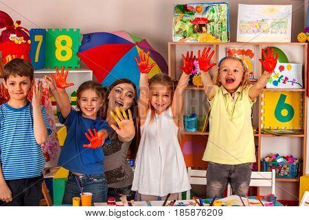 Small students with teacher finger painting in art school class. Teacher cheers children in kinderga