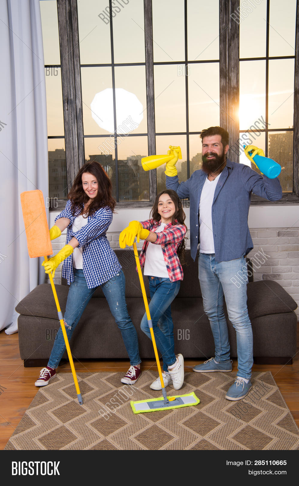 Family Mom Dad And Daughter With Cleaning Supplies At Living Room. We Love Cleanliness And Tidiness.