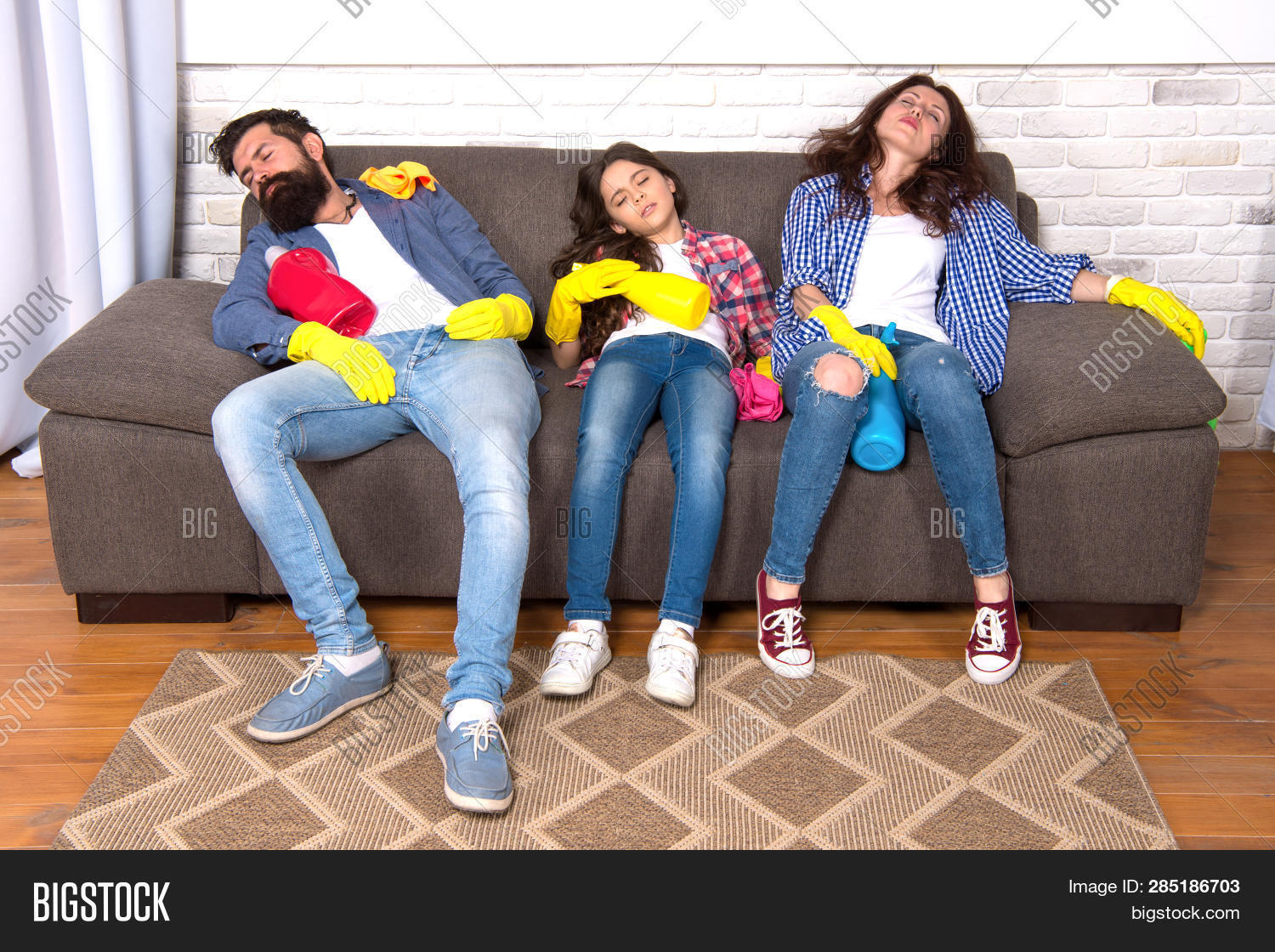 Exhausting Cleaning Day. Family Mom Dad And Daughter With Cleaning Supplies Sit On Couch. Family Car